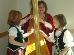Harpist Anita Burroughs-Price with interested observers, Cameron Village Regional Library